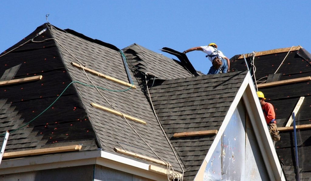Employee of Bowling Roofing applying new black shingles on a steep roof.