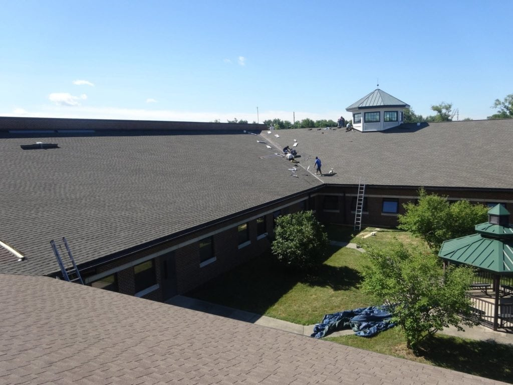 Large commercial job with grey shingles nearing completion by Bowling Roofing.