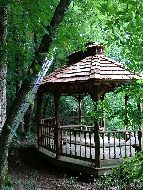Gazebo with brown shingles from Bowling Roofing in the woods.