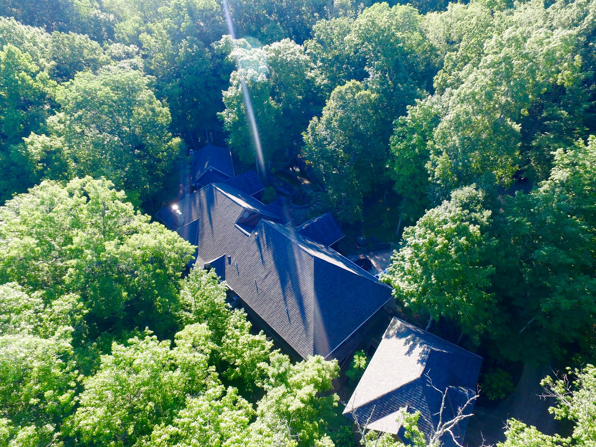 Aerial view of newly shingled grey roof on a large residential property surrounded by beautiful green trees.