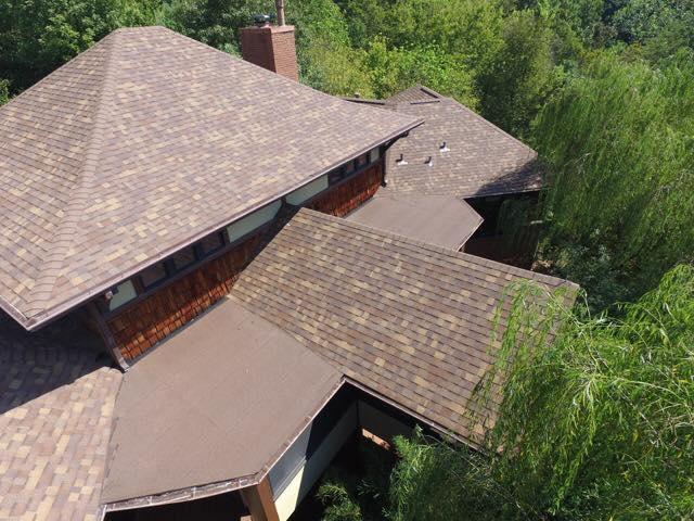 Newly completed brown roof completed by Bowling Roofing, surrounded by beautiful greenery.