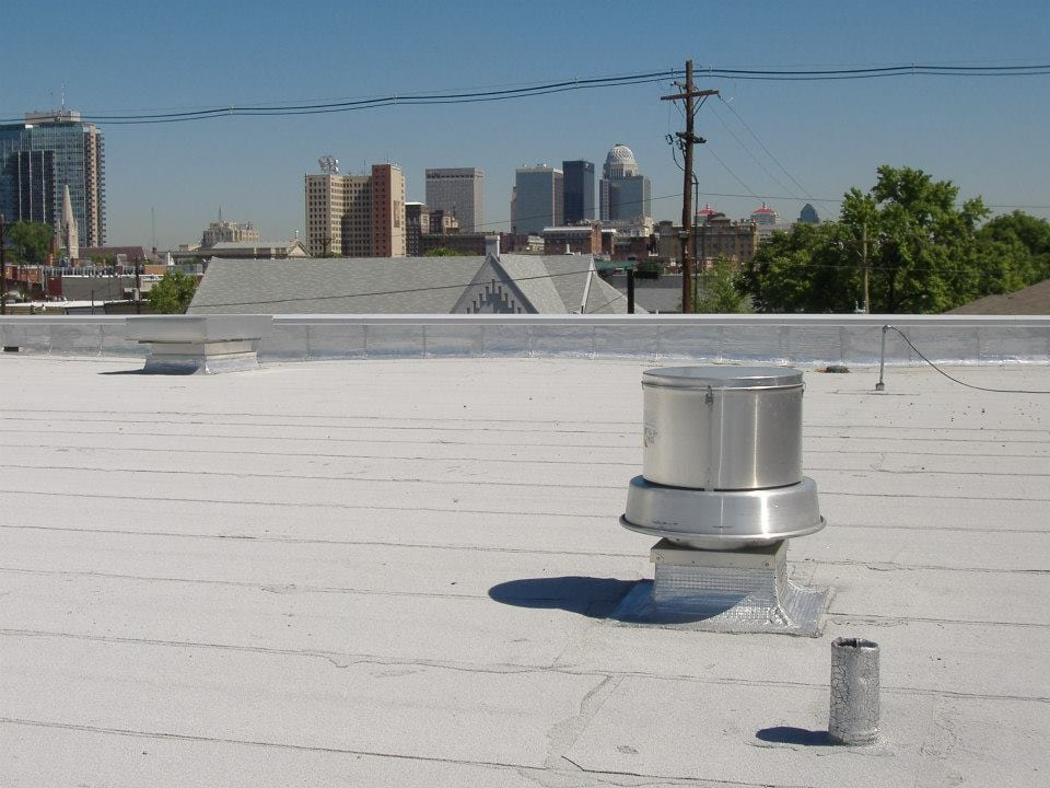 Silver chimney cap upon the roof of a commercial building.