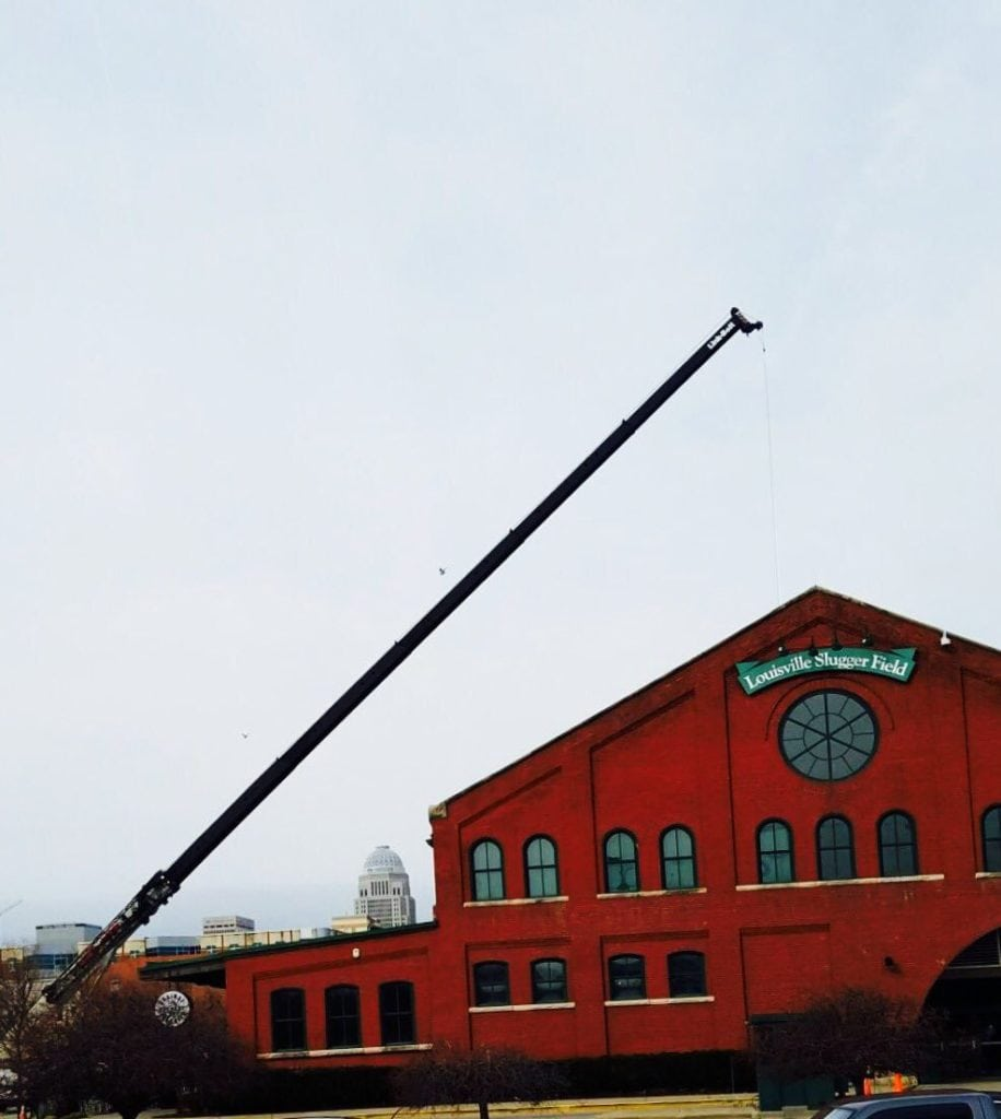 Bowling Roofing using a large crane to help replace the roof of a beautiful red building.