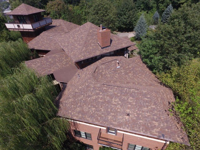 Brown Shingled residential roof completed by Bowling Roofing on a sunny day.